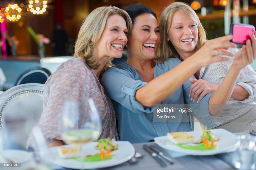 Female friends taking selfie in restaurant