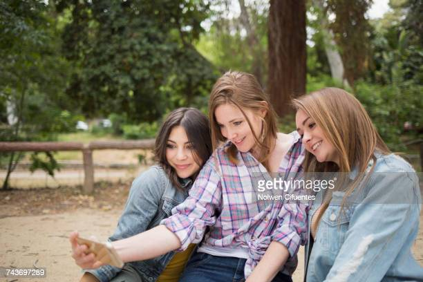 Female friends taking selfie thorough smart phone at park