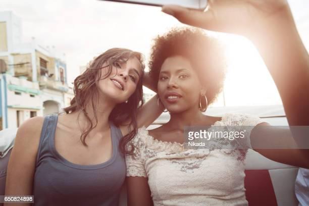 Female friends taking selfie while sitting in convertible, Malecon, Havana, Cuba