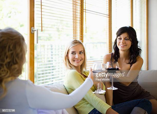 Female friends talking and drinking wine at home.