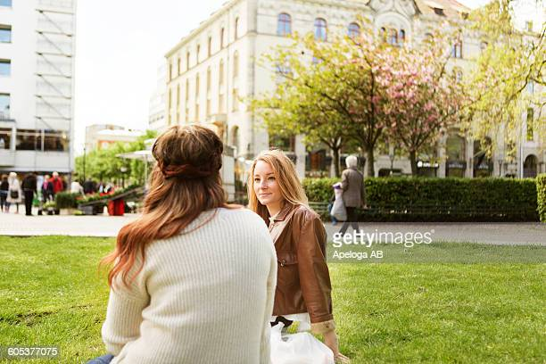 Female friends talking while sitting on grassy field at park