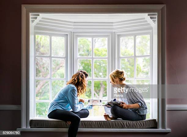 Female friends using digital tablet on window sill