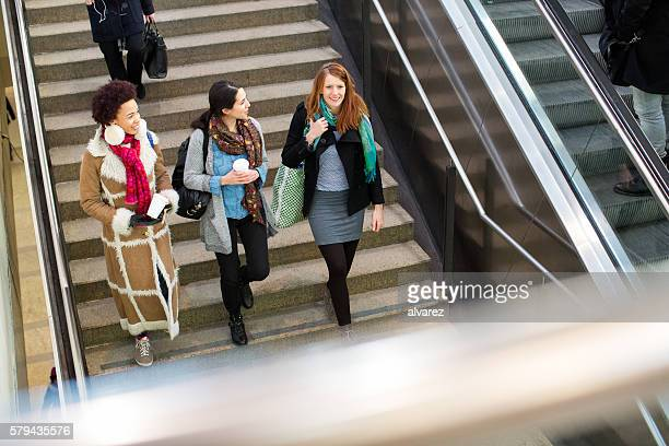 Female friends walking down the stairs at subway station