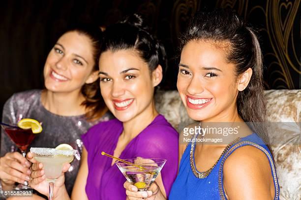 Weibliche Freunde sitzen zusammen mit Cocktails In Nachtclub