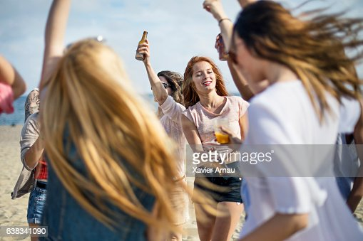 Female friends with drinks dancing at beach  Stock Photo