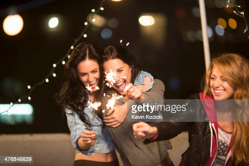 Female friends with sparklers at rooftop party