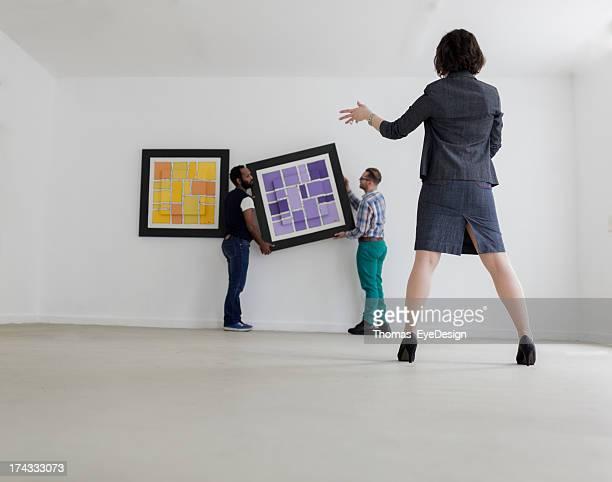 Galeriebesitzerin beim Aufhängen eines Kunstwerks