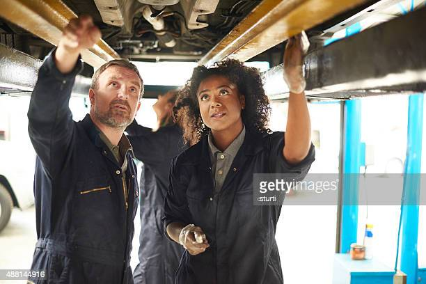Female garage mechanic trainee with her teacher