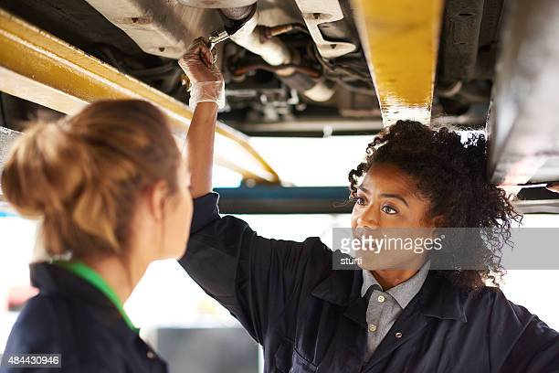 female garage mechanics under a car