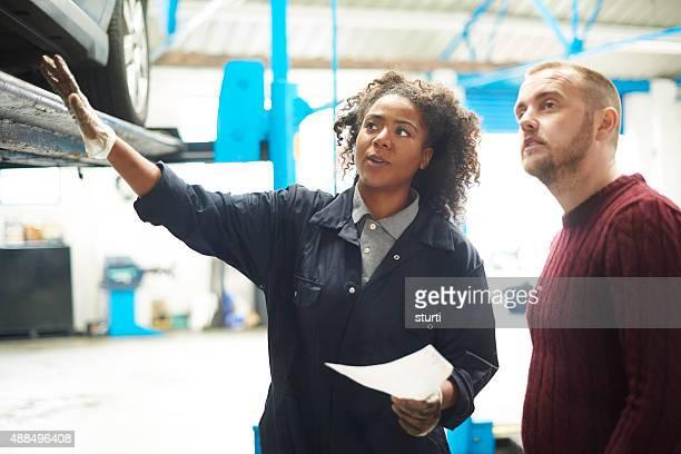 female garage owner explains bill to customer