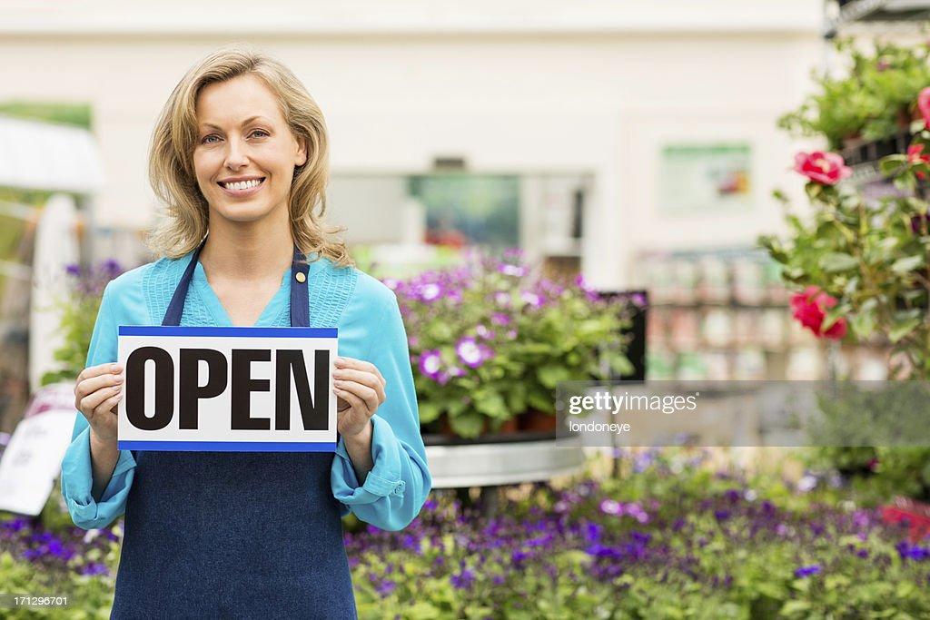 Female Garden Worker Holding an Open Signboard : Stock Photo
