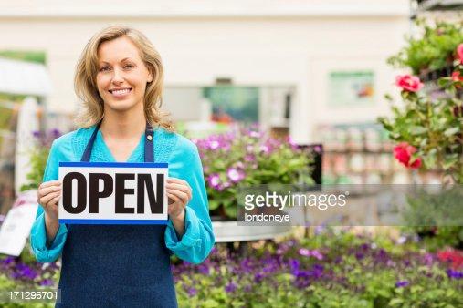 Female Garden Worker Holding an Open Signboard