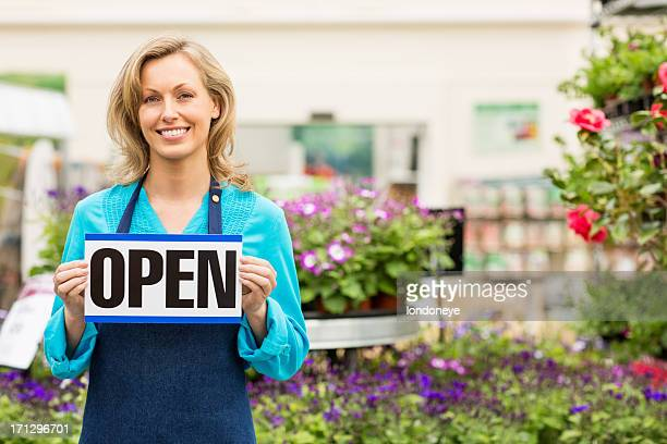 Female Garden Worker Holding an Open Signboard