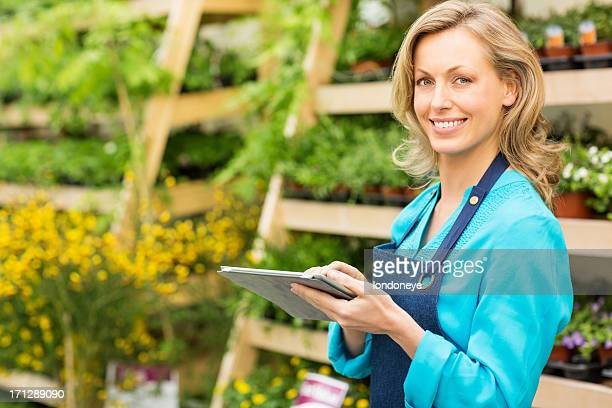 Female Garden Worker Using Digital Tablet