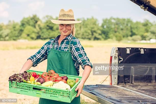 Female gardener holding box of fresh vegetables