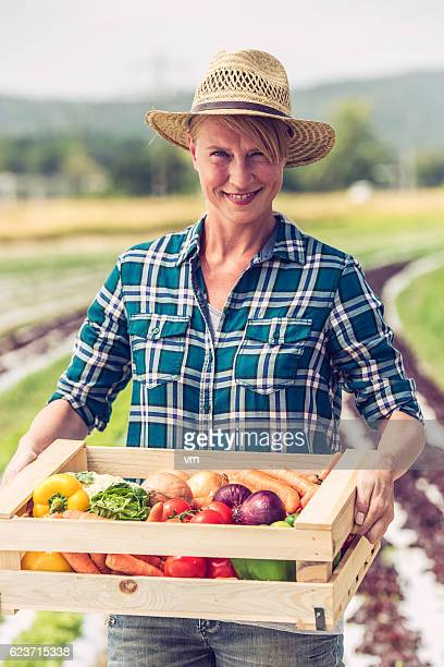 Female gardener holding crate of vegetables