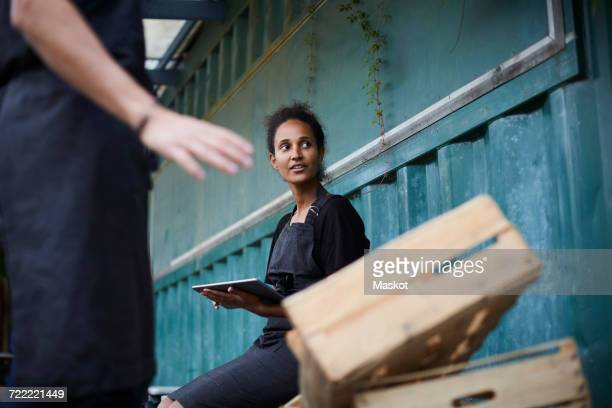 Female gardener holding digital tablet while friend gesturing by crates