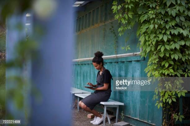 Female gardener using digital tablet while sitting on bench