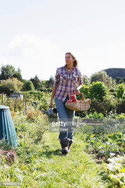 female gardener walking in allotment with basket a