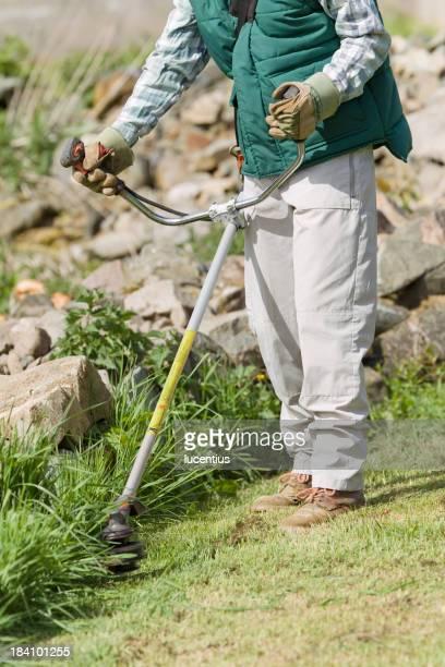 Female gardener with strimmer in garden