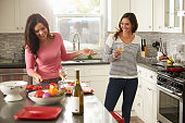Female gay couple preparing meal together and drinking wine