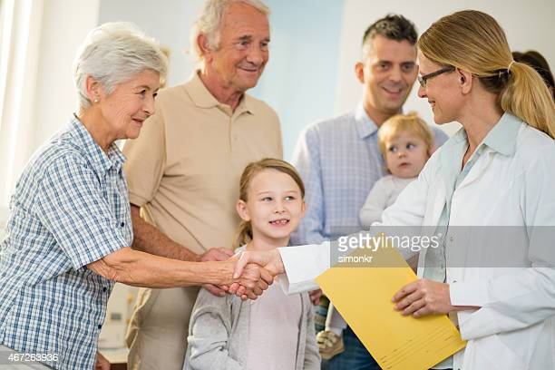 Female General Practitioner Shaking Hands With Patients