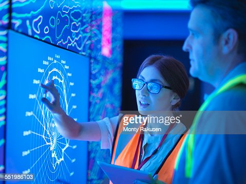 Female geologist with colleague studying graphical display of oil and gas bearing rock on screens