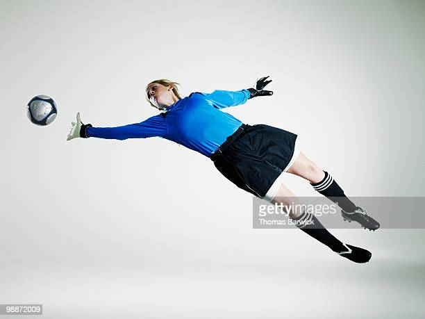 Female goalie diving in mid air for soccer ball