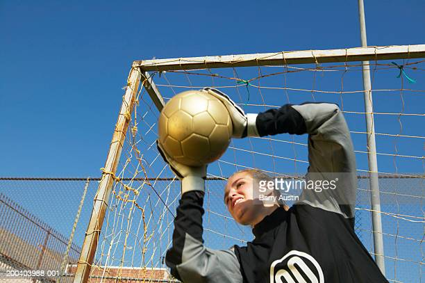 Female goalie (12-14) holding ball, low angle view