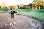 A shot of a young girl hitting the ball out of the bunker during a round of golf.