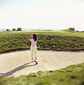 Female golfer playing in sand trap, rear view