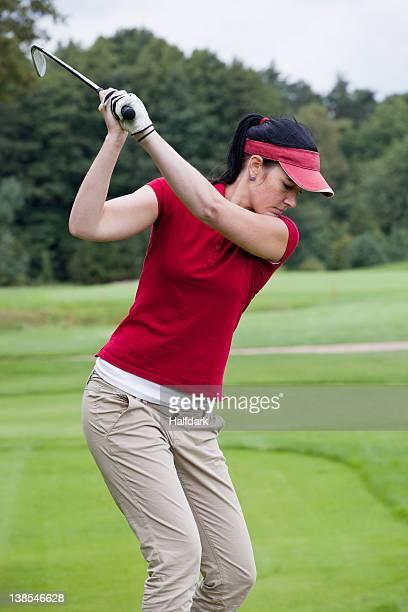 A female golfer preparing to swing her club