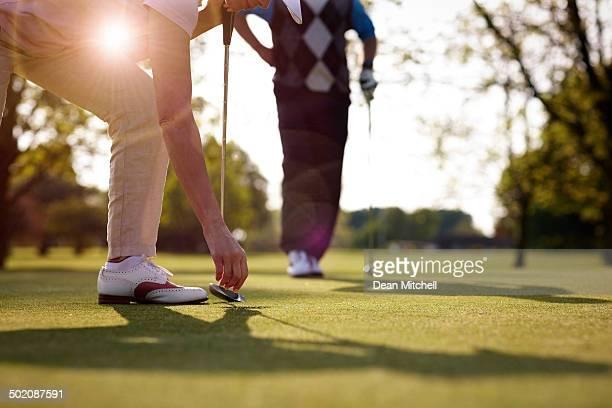 Female golfer retrieving golf ball from hole