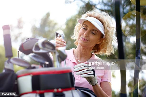 Female golfer selecting the right club for a perfect shot
