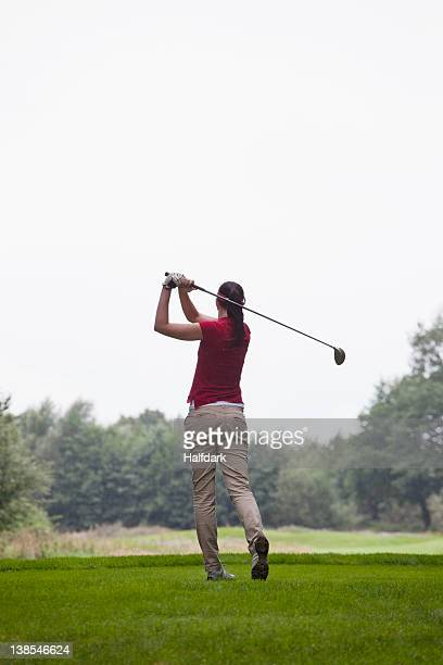 A female golfer teeing off, rear view
