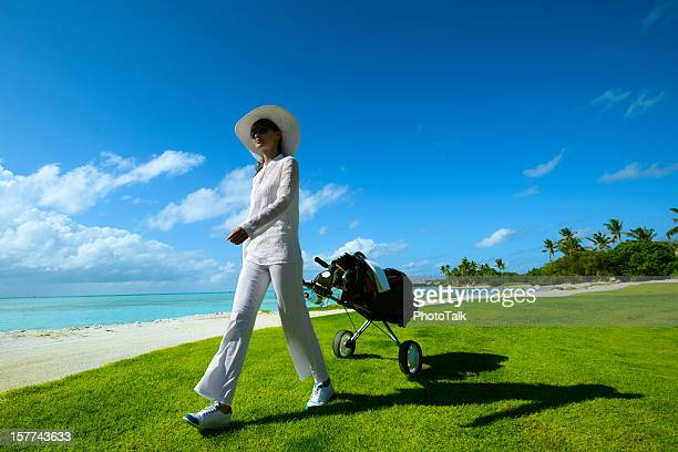 Female Golfer With Cart Walking On Beach Golf Course