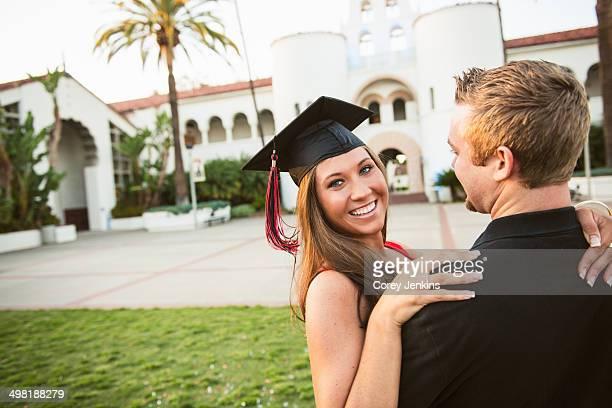 Female graduate hugging man