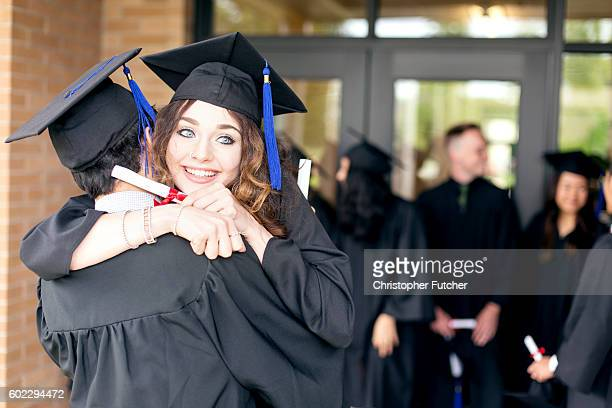Female graduate hugs her classmate