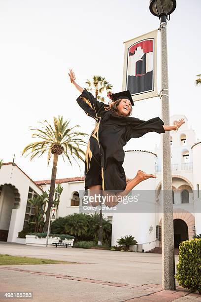 Female graduate jumping for joy
