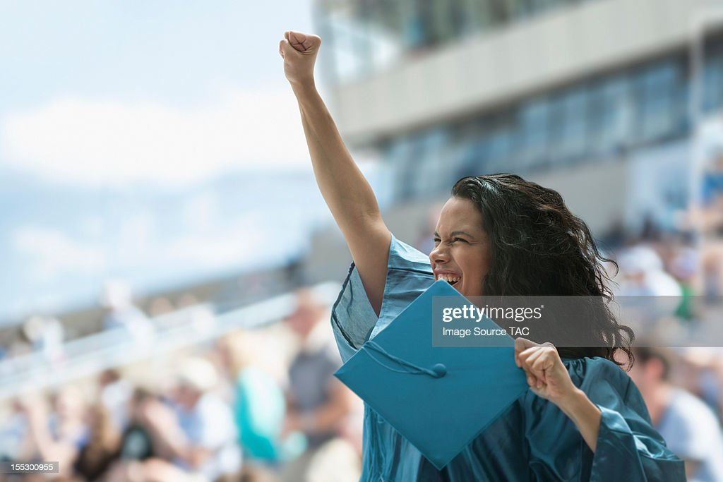 Female graduate raising fist : Stock Photo