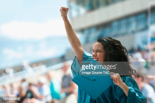 Female graduate raising fist : Stock Photo