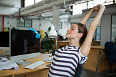 Female graphic designer sitting on chair and stretching her arms in creative office