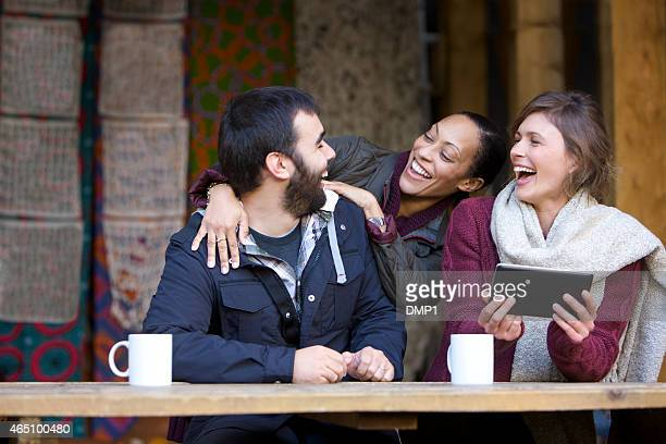 Female greeting her friends upon arrival at an outdoor cafe