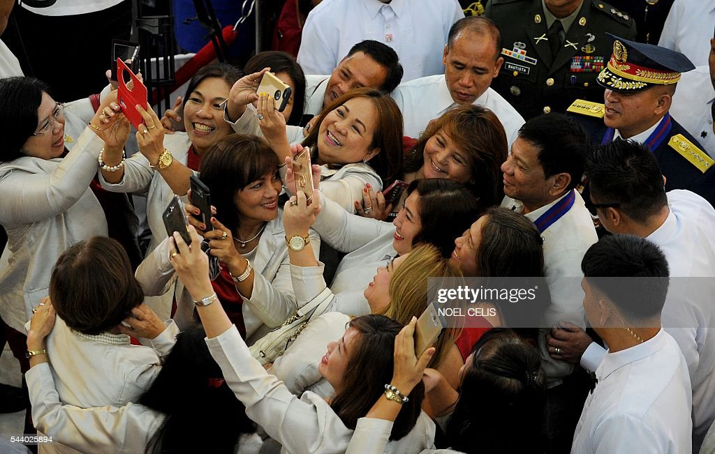 Female guests take selfies with President Rodrigo Duterte during Philippine National Police (PNP) chief Ronald Bato Dela Rosa's Assumption of Command Ceremony at the Camp Crame in Manila on July 1, 2016. Authoritarian firebrand Rodrigo Duterte was sworn in as the Philippines' president on June 30, after promising a ruthless and deeply controversial war on crime would be the main focus of his six-year term. / AFP / NOEL