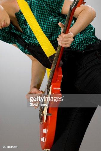 Female guitarist playing a guitar : Foto de stock