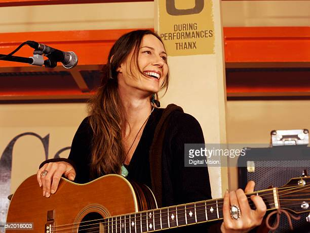 Female Guitarist Stands by a Microphone Stand on a Stage, Laughing