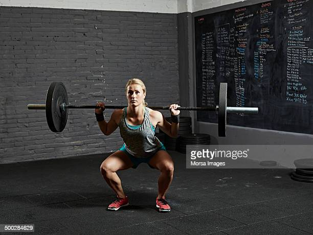 Female gym performing back squat