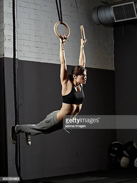 Female gym training with gymnastics rings