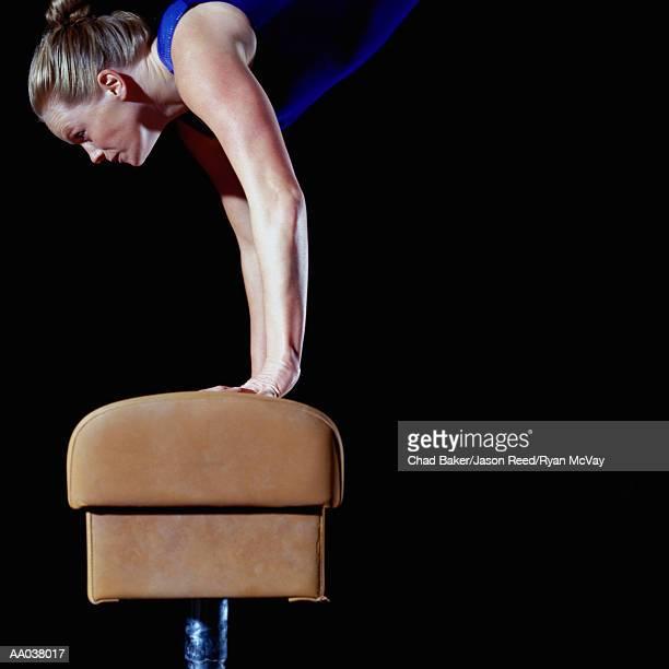 Female gymnast balanced on vault, side view