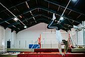 Female gymnast doing a handstand on a balance beam